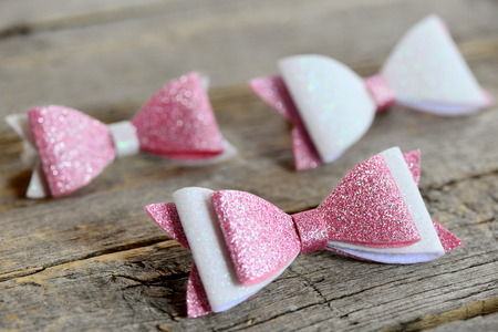 Lovely beautiful bows for hair. Pink and white shiny felt bows for girls. Beautiful hair accessories set on a wooden table Stock Photo