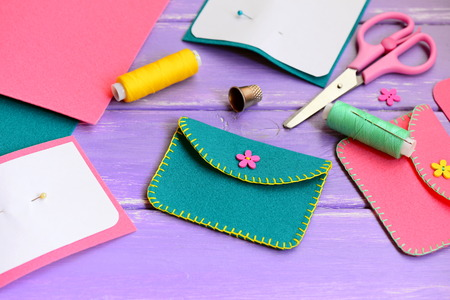 learning new skills: Cute green and pink felt with flower buttons. Scissors, thread, needle, thimble, paper templates on a wooden table. Hand sewing workshop concept Stock Photo
