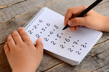 Kid solves multiplication examples. Kid holds a marker in his hand and writes answers to multiplication. Children math education concept Stock Photo