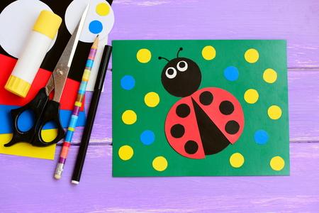 pasteboard: Bright ladybug cardboard card. Green card with ladybug, scissors, glue stick, pencil, marker, cardboard set on a wooden table. Summer homemade card idea to make. Closeup