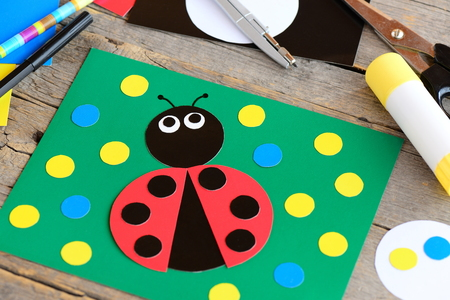 Cute ladybug cardboard card. Green card with ladybug made from cardboard, scissors, glue stick, pencil, marker, cardboard sheets on a wooden table. Summer crafts idea for kids. Closeup