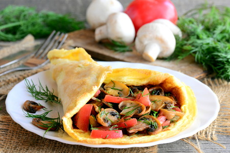 Ruddy omelet stuffed with fried mushrooms, fresh tomato slices and dill herbs. Home stuffed omelet on a plate. Rustic style Stock Photo