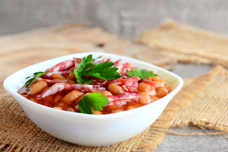 Smoked sausages with white beans in classic tomato sauce. Tasty white beans and smoked sausage stew in a white bowl and on a burlap textile. Rustic style. Home stew Stock Photo