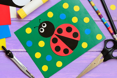 Bright ladybird card. Green card with ladybird, scissors, glue stick, pencil, marker, cardboard set on a wooden table. Summer homemade cards for kids to make. Closeup