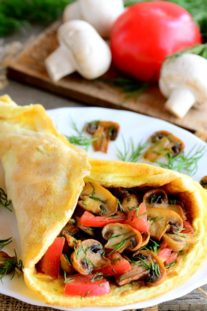 healthful: Mushroom and tomato omelet on a white plate. Egg omelet stuffed with mushrooms, tomatoes and dill. Light summer lunch or diner idea. Vertical photo