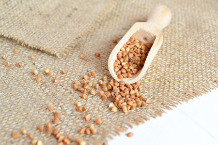 caloric: A spoon of raw buckwheat on a burlap and a white wooden background Stock Photo