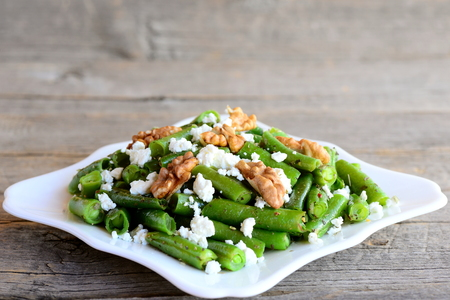 long bean: Green string beans with homemade cottage cheese and walnuts on a white plate and vintage wood background. Closeup