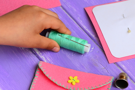 Small child made a felt purse. Sewing supplies on a wooden table. Funny and simple sewing craft for kids to do