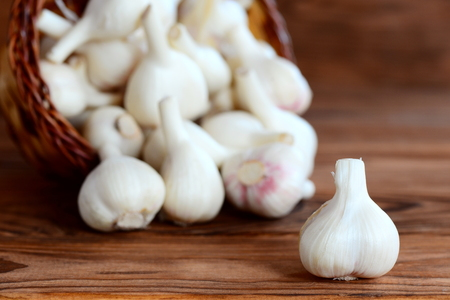 Raw young garlic in a basket on a wooden background. Aromatic product, health food. Closeup Stock Photo