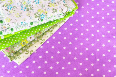 Green fabric on purple background. Material sewing fabric. Pattern fashion sewing fabrics. Sewing fabric set. Sewing supplies for beginners. Sewing supplies aesthetic photo