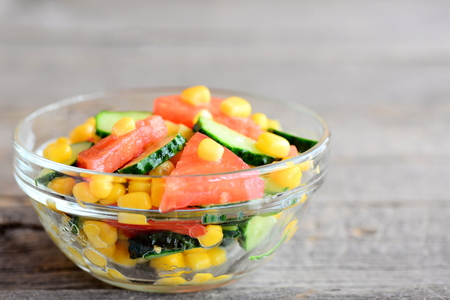 Salad with fresh tomatoes, cucumbers and canned corn dressed with olive oil and lemon juice. Vegetable salad in a bowl on an old background with copy space for text. Closeup