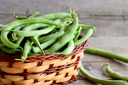 Green string beans in a wicker basket. Fresh young beans pods. Vintage wooden background. Harvest concept. Closeup