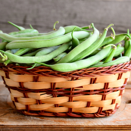 Green string beans in a wicker basket and a wooden board. Raw young beans pods. Old wooden background. Seasonal harvest concept. Closeup Stock Photo