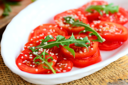 old desk: Tomato and arugula salad recipe. Home fresh tomatoes, arugula and sesame seeds salad on a white plate. Quick and healthy vegetarian salad recipe. Closeup Stock Photo