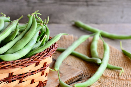 Raw green beans in a brown basket and on a burlap textile. Fresh young beans pods. Old wooden background. Green string beans crop conception