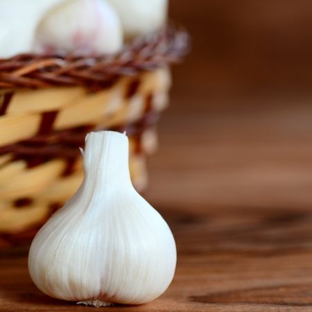 Raw garlic bulbs in a basket on a wooden background with copy space for text. Harvesting garlic plants concept. Garlic background. Closeup Stock Photo