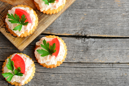 Home mini sandwiches with cream cheese on a wood background with empty place for text. Quick mini sandwiches from crackers cookies, spicy cream cheese, tomato and parsley. Tasty snack recipe. Top view Stock Photo