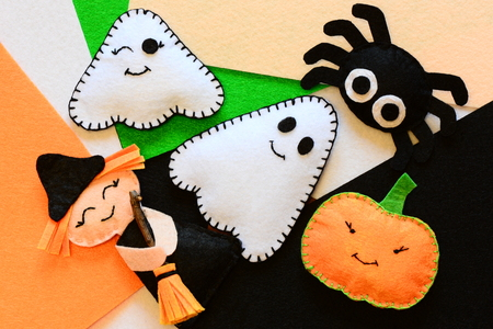 Halloween cute felt ornament decor. Small witch with broom, pumpkin head, two ghosts, spider. Halloween toys. Simple kids sewing crafts concept. Top view
