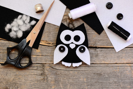 Black and white felt owl, felt sheets, scissors, threads, thimble, buttons on a vintage wooden table. Creating pretty owl ornament from felt. Felt craft used in kids handicraft. Top view