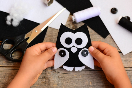 Child holds a felt owl in his hand. Small child made of owl out of black and white felt. Teaching children simple sewing skills at home. Sewing concept