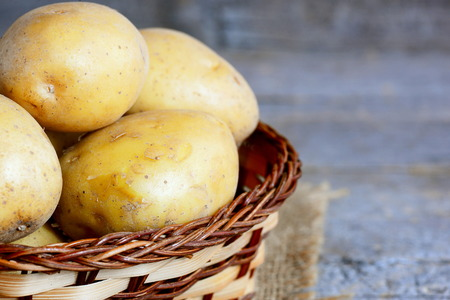 Fresh new potatoes. Raw new potato in a wicker basket on a vintage wooden table. Closeup Stock Photo
