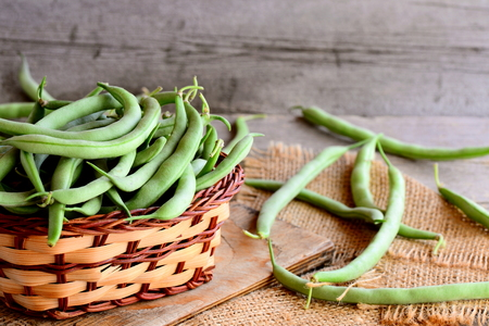 Long green beans in a brown wicker basket on a wooden board and a burlap textile. Vintage wooden background Stock Photo