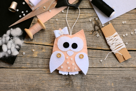 Nice felt owl ornament, sewing supplies and tools on a vintage wooden table. Creating a christmas ornament from felt. Simple childrens sewing crafts for Christmas. Top view