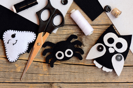 Halloween felt decorations. Felt ghost, spider, owl decorations on a vintage wooden table. Sewing tools and materials. Easy at home craft projects to make with felt sheets. Top view. Closeup