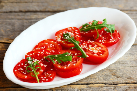 Salad with sliced ??tomato, rucola, sesame seeds. Quick tomato salad on a white plate isolated on an old wooden background. Sliced ??tomato salad recipe. Closeup Stock Photo