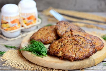 Spicy chicken liver patties with vegetables. Brown fried chicken liver patties on a wooden cutting board. Easy chicken liver recipe idea. Closeup