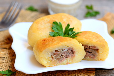Potato zrazy with a meat filling on a white plate and a vintage wooden table. Traditional Ukrainian zrazy recipe. Closeup Stock Photo