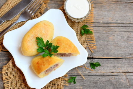 Fried potato zrazy stuffed with a meat on a white plate. Sour cream, fork, knife on a vintage wooden table. Homemade zrazy recipe. Wooden background with copy space for text. Top view