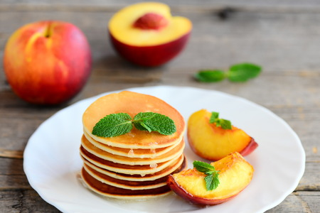 Basic pancakes with syrup and grilled nectarines on a serving plate and an old wooden table.