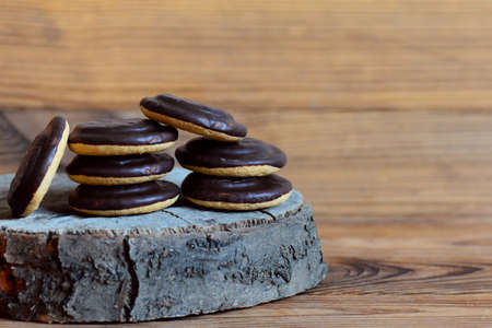 Cookie stack on a wooden background. Round biscuits in chocolate glaze. Closeup. Chocolate cookie photo. Chocolate biscuits. Chocolate cookie. Dessert. Cookies with chocolate icing