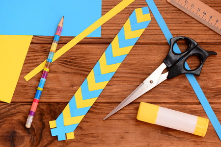Yellow and blue paper bookmark. Scissors, glue stick, colored paper sheets, ruler, pencil on a wooden table. Light paper art projects. Paper craft for kids with folding paper. Top view Stockfoto