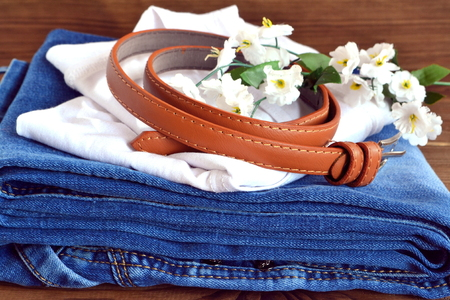 Jeans, t-shirt, belt - clothing set on wooden background Stock Photo