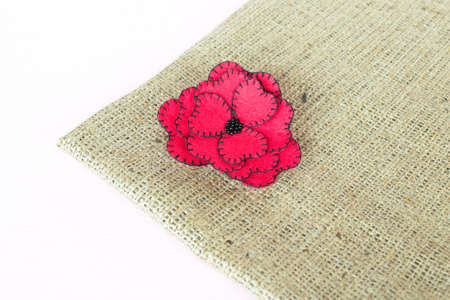 Red felt flower on burlap and white wooden background