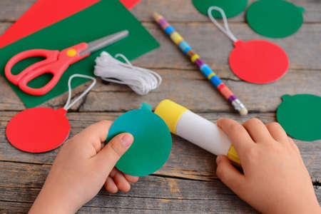 Child makes Christmas balls out of cardboard. Child carves and glues Christmas balls from cardboard. Step. Stationery on the table. Paper Christmas ornaments kids craft. Winter craft activities