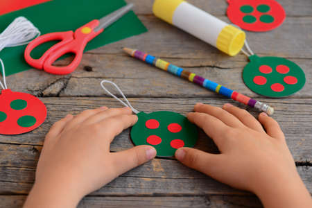 Child made bright Christmas balls from cardboard paper. Child shows Christmas ball. Step. Scissors, pencil, glue stick on an old wooden table. Homemade easy Christmas tree decorations for children 版權商用圖片
