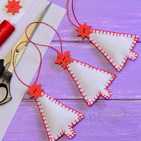 Christmas tree decorations, craft materials and tools on a purple wooden background. Simple crafts made of felt. Hand sewing idea. Christmas wall and hanging decoration. Top view. Closeup