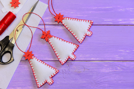 learning new skills: Christmas tree decorations, craft materials and tools on a wooden background with copy space for text. Easy handmade felt crafts for kids. Christmas sewing projects for holidays. Top view
