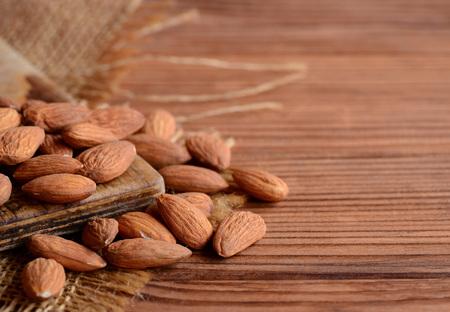 albero nocciolo: Mandorle pelate Un mucchio di mandorle crude su un tavolo di legno. Foto di noci Stile country
