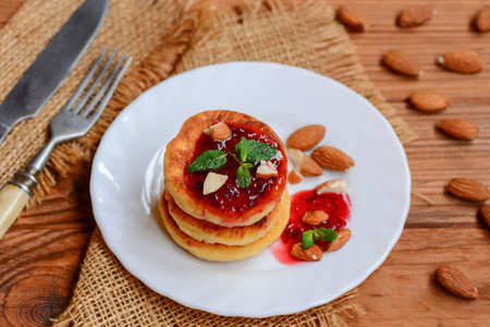 Fried cottage cheese pancakes with berry jam, almonds nuts and mint on a served plate. Delicious cottage cheese almond flour pancakes. Homemade cheese fritters. Fried cheese fritters. Sweet syrniki