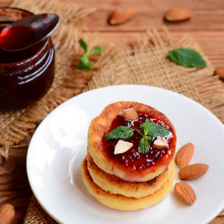 Sweet cottage cheese pancakes with berry jam, almonds nuts and fresh mint on a serving plate. Simple breakfast pancakes recipe. Closeup. Easy healthy breakfast recipe. Breakfast food idea 版權商用圖片