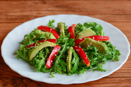 Avocado, arugula and pepper salad on a white plate. Simple arugula and avocado salad with red pepper and sesame seeds. Raw food menu. Closeup. Raw meal diet plan for weight loss. Raw dietl plan