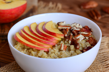 pekan: Sweet quinoa porridge with fruits and nuts. Vegan quinoa porridge with fresh apples and pecans in a white bowl. Rustic style. Closeup Stock Photo