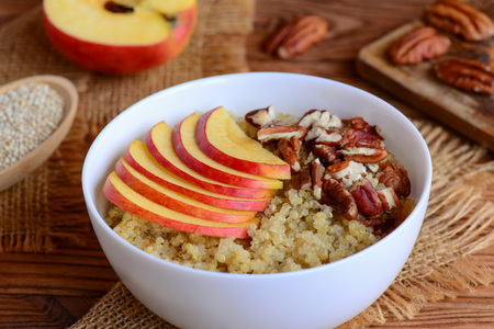 pekan: Quinoa porridge with fruits and nuts. Healthy quinoa porridge with fresh apples and pecans in a white bowl. Rustic style. Closeup