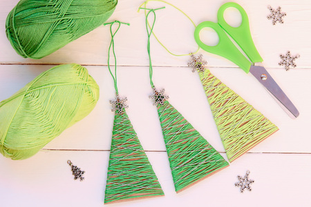 Christmas trees ornaments on a wooden background. Simple Christmas trees ornaments made of old cardboard box and cotton yarn. Creative recycling idea for home or school
