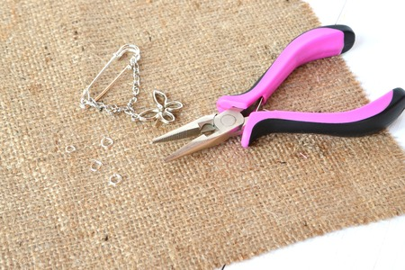 Brooch, metal charms, connecting ring, the pliers on burlap and white wooden background Stock Photo