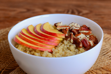 Quinoa porridge with fresh apples and nuts. Vegetarian quinoa porridge with apples and pecan nuts in a white bowl. Sweet dish. Rustic style. Closeup